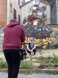 Producer Paul Hutson stands in for a shot in front of a Stefan Ways mural and instillation. Kyle Deitz camera operates on a Ronin.